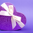 Single heart gift box with ribbon on blue background. — Foto de Stock