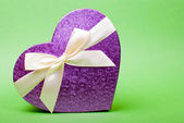 Single heart gift box with ribbon on green background. — Stock Photo