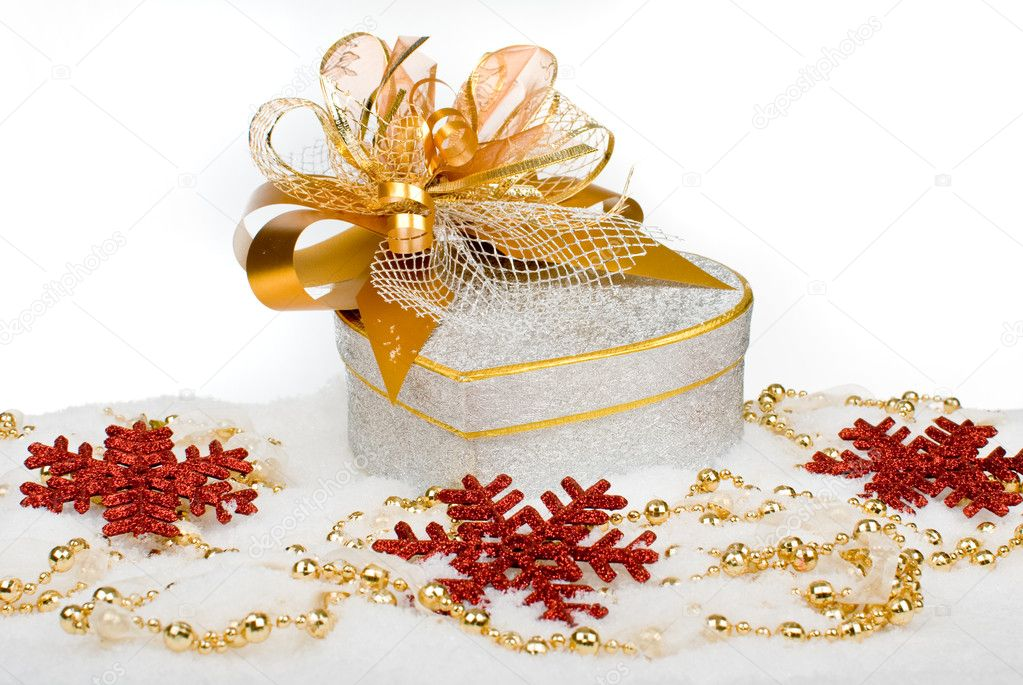 Christmas silver heart gift box with golden ribbon in snow on a white background. — Zdjęcie stockowe #9827464