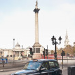 Stock Photo: Taxi on Nelsons Column at London, England