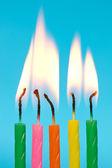 Födelsedag ljus brinna på blå bakgrund — Stockfoto