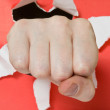 Hand punching through red paper — Stock Photo