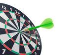 Green dart hitting target center — Stock Photo