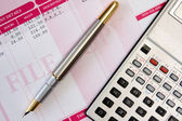Ink pen,calculator and payslip — Stock Photo