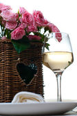 Glass of white wine and a basket of roses — Stock Photo