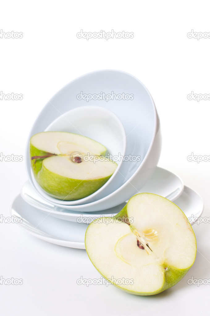 Two halves of a large green apple on a stack of white plates — Stock Photo #9644656