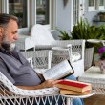 adam okuma İncil verandada — Stok fotoğraf