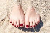 Womans feet in sand — Stock Photo