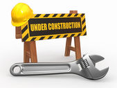 Barrier with text under construction and hardhat — Stock Photo