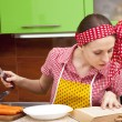 Woman in the kitchen with knife recipe book — Stock Photo