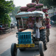 Smiling workers on the overfull by sacks tractor, India - Stock Photo