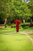 Buddhism monk in red clothes follows the path — Stock Photo
