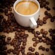 Close-up cup of hot coffee and coffee beans — Stock Photo