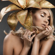 Portrait of woman with golden flower — Stockfoto