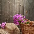 Basket of flowers and a straw hat — Stock Photo