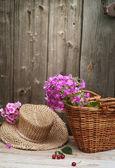 Košík květin a slaměný klobouk — Stock fotografie