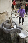 Woman grinding soybeans to production of milk — Stock Photo