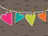 Colorful hearts hanging on a line against wall . — Stock Vector