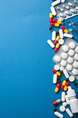Pills border over blue — Stock Photo