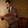 Man in suit reading newspaper — Stock Photo