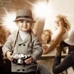 Baby boy with retro camera over photo shoot background. — Stock Photo