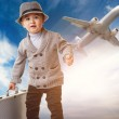 Baby boy with a briefcase against airplane — Stock Photo