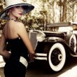 Woman in hat against retro car - Lizenzfreies Foto