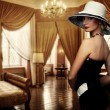 Beautiful woman in hat in luxury room — Stock Photo #10204491