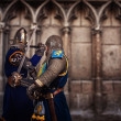 Two knights fighting agaist medieval cathedral wall — Stock Photo #10204854