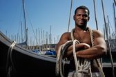 Handsome afro-american sailor against boats. — Stock Photo