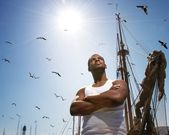 Handsome afro-american man against boat's mast. — Stock Photo