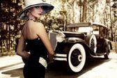 Kobieta w kapeluszu przed samochód retro — Zdjęcie stockowe
