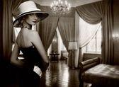 Vacker kvinna i hatt i lyxiga rum. — Stockfoto