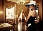 Beautiful woman in hat in luxury room — Stock Photo