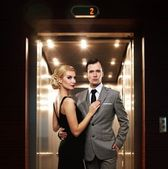 Retro couple standing against elevator. — Stock Photo