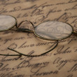 Old glasses on the vintage document - Stock Photo