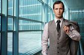 Man in grey suite in modern building. — Stock Photo