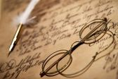 Glasses and inkwell on an old letter — Stock Photo