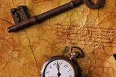 De oude sleutel met een klok op de geweven papier — Stockfoto