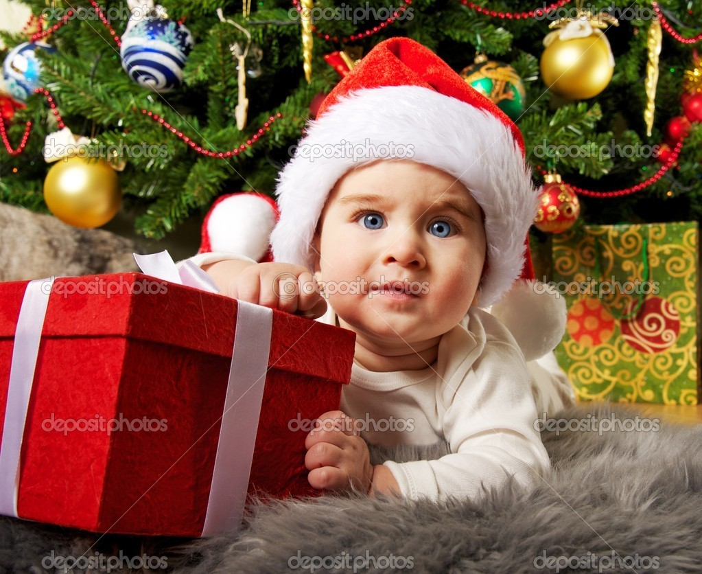Santa baby playing with gift box — Stock Photo #8601166