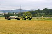 Le tracteur avec la remorque passe à travers le champ — Photo