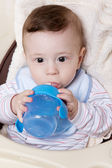 Adorable little baby boy with feeder — Stock Photo