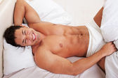 Happy man lying in his bed — Foto de Stock