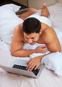Young man using laptop at the bedtime — Stock Photo