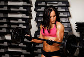 Sportswoman is holding fitness bar — Stock Photo