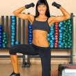 Beautiful woman is doing exercises in the sport club. - ストック写真