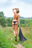 Naked woman walking at the meadow — Stock Photo