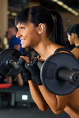 Beautiful woman is doing exercises with the bar — Stock Photo