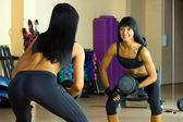 Hermosa mujer está haciendo ejercicios en el espejo. — Foto de Stock