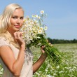 Beautiful woman at the meadow with bunch of chamomiles. — Stock Photo